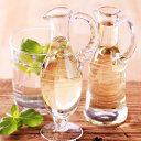Zwei Glaskaraffen und Glas Weißweinessig