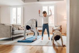 Ein Vater macht zu Hause Sport mit seinen beiden Kindern.
