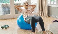 Seniorin trainiert ihr Gleichgewicht mit Übungen auf einem Gymnastikball.