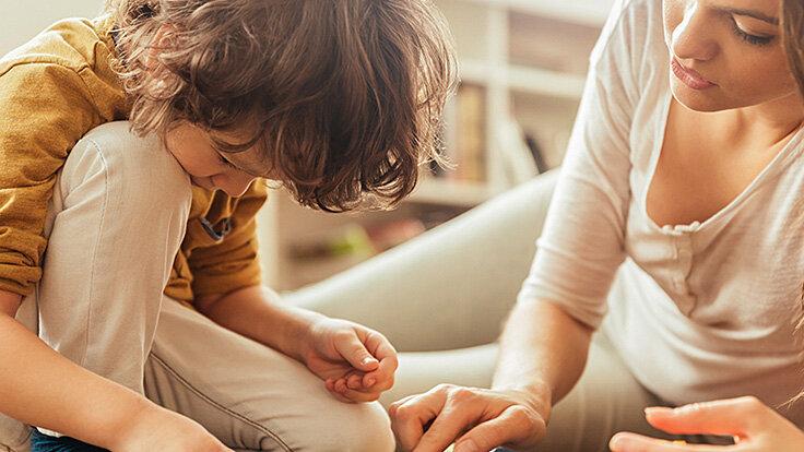 Mutter und Sohn spielen zusammen auf dem Boden.
