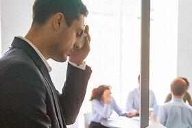Ein Mann ist nervös vor einem Vortrag im Büro und tupft sich den Schweiß von der Stirn.