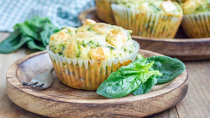 Herzhafte Muffins mit Spinat und Feta auf einem Holzteller serviert