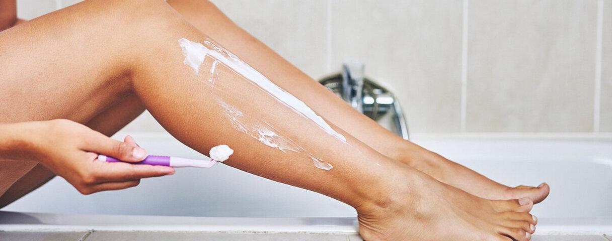 Eine Frau benutz im Bad einen Rasierer.