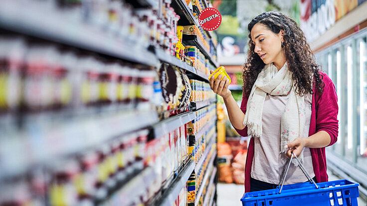 Eine junge Frau liest im Supermarkt die Zutatenliste von einem Produkt aus dem Supermarktregal.