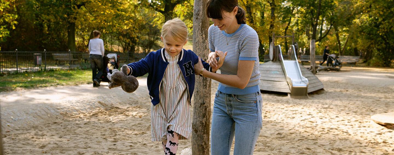 Loben- Mutter und Kind auf dem Spielplatz.