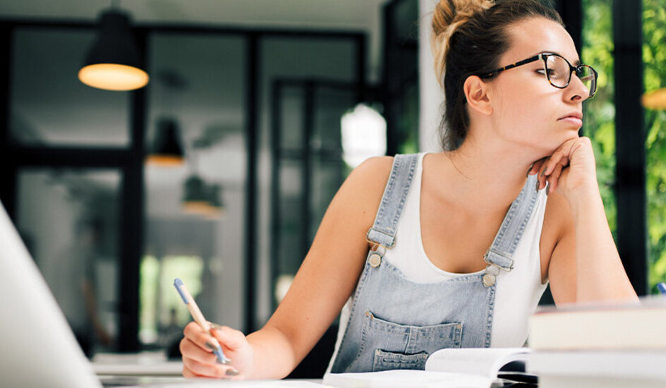 Eine Frau sitzt am Schreibtisch und prokrastiniert.
