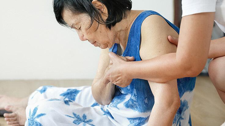 Eine Frau ist wahrscheinlich durch Schwindel zusammengebrochen und wird von einer Frau gestützt, die ihr aufhelfen möchte.