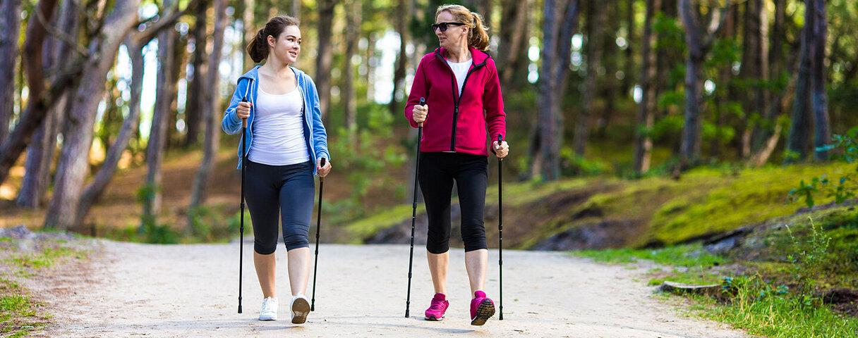 Zwei Frauen beim Nordic Walking im Wald mit Trekkingstöcken.