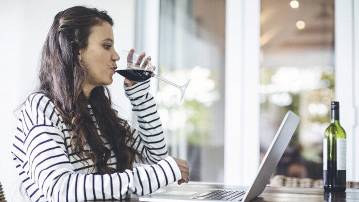 Eine Frau sitzt am Tisch vor dem Laptop und trinkt Rotwein.