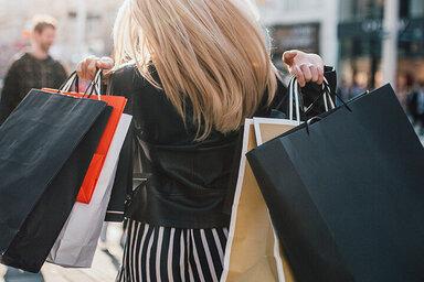 Eine Frau trägt mehrere Einkaufstaschen über den Schultern und schlendert durch eine Einkaufsstraße zum Shoppen