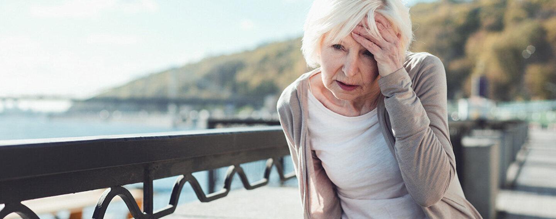 Einer Dame ist schwindelig und sie muss sich an einer Brüstung festhalten, weil sie einen Schlaganfall hat.