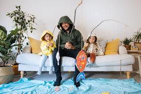 Vater spielt mit seiner Tochter und ihrer Freundin im Wohnzimmer, so hilft er, die Kinderfreundschaft aufzubauen.