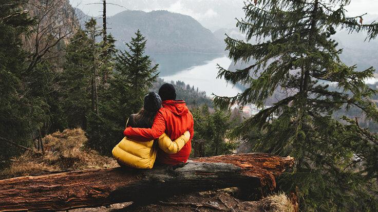 Ein Mann und eine Frau sitzen auf einem Baumstamm in einer Berglandschaft und umarmen sich. Sie schauen auf ein Tal und einen See.