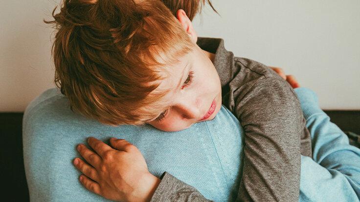 Ein Kind ist auf dem Arm genommen und traurig – jemand in der Familie ist schwerkrank. Wie man mit dem Tod umgeht.