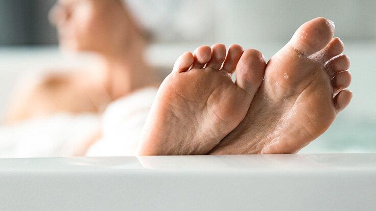 Eine Frau liegt in der Badewanne und streckt die Füße aus.