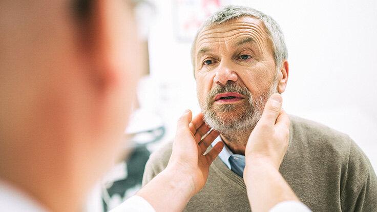 Ein Arzt untersucht einen Mann am Hals.