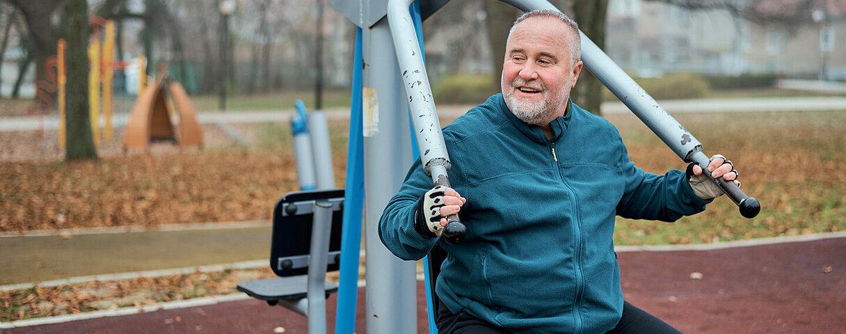 Ein Mann macht Sportübungen an Fitnessgeräten im Park.