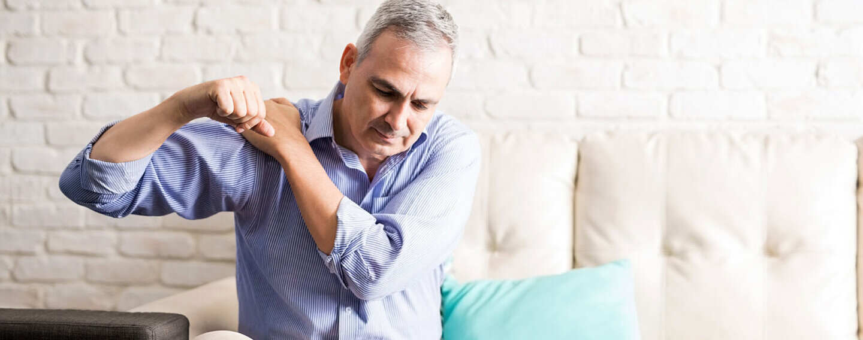 Ein Mann sitzt auf der Couch und kreist die Schulter, er hat Schmerzen.