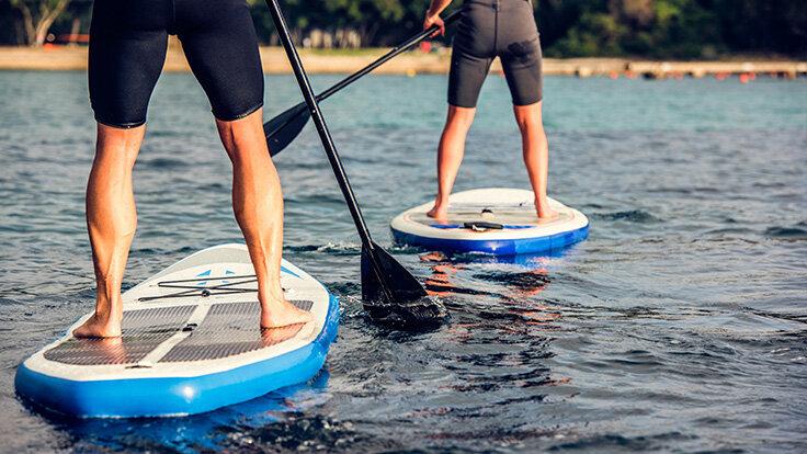 Zwei Personen stehen breitbeinig auf eine breitem Board für SUP.
