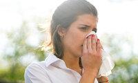 Eine Frau ist im Freien und putzt sich die Nase.