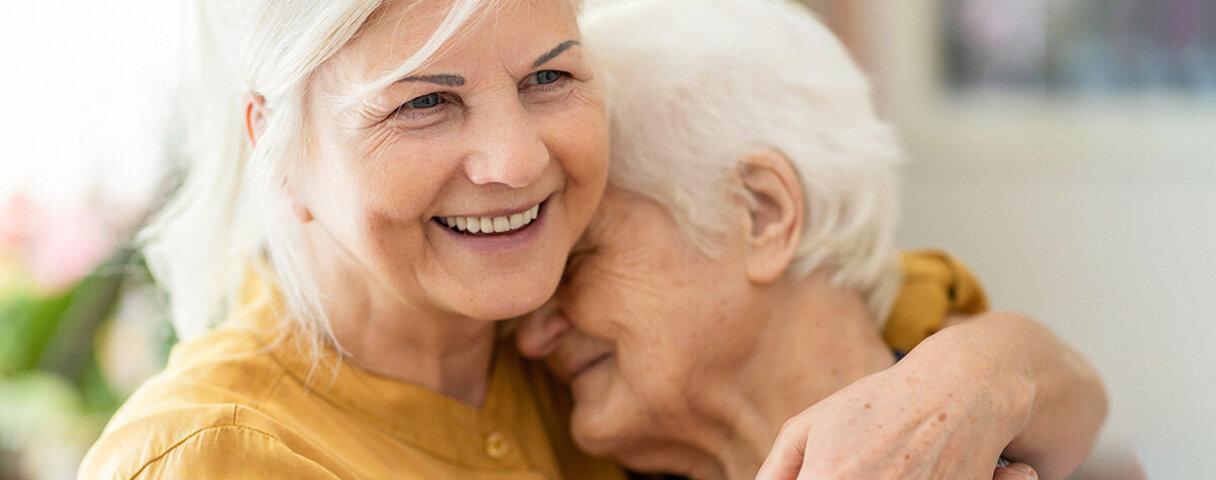 Zwei Frauen umarmen sich. Seit der Krebsdiagnose achten sie mehr auf sich selbst und den anderen.