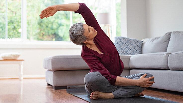 Eine ältere Frau macht Dehnübungen auf einer Yogamatte.