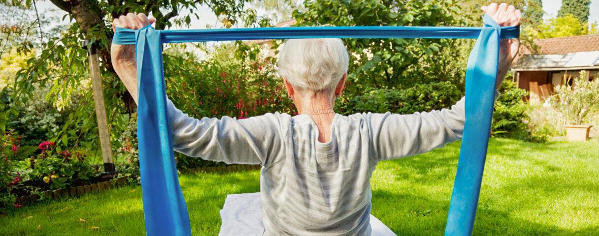 Eine ältere Frau trainiert mit einem Fitnessband im Sitzen.