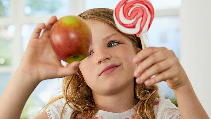 Kind hat die Wahl zwischen einem Apfel und einem süßem Lolli.