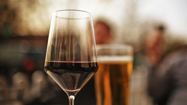 Ein Rotweinglas steht im Vordergrund, im Hintergrund ein Glas Bier.