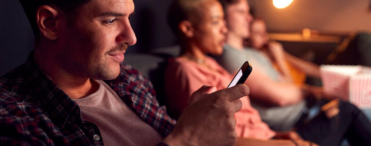 Ein Mann sitzt mit Freunden auf der Couch und checkt sein Smartphone aus Angst, etwas zu verpassen.
