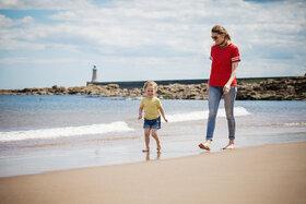 Eine Mutter und Kind sind am Strand an der Nordsee und spazieren.