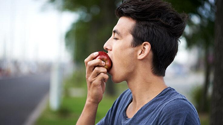 Junger Mann genießt achtsam und bewusst einen Apfel.