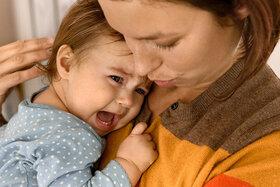 Schreibaby weint im Arm der Mutter