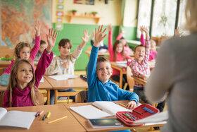 Schüler sitzen in der Klasse und heben die Hand, um dem Lehrer zu antworten.