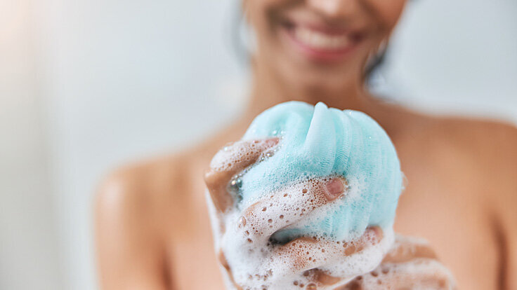 : Eine junge Frau hält bei ihrer täglichen Dusche einen schäumenden Schwamm in der Hand.