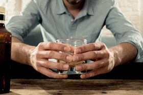 Mann sitzt auf der Couch und schaut auf ein Glas mit Alkohol.