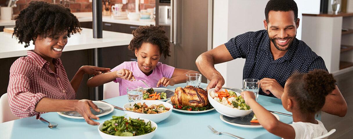 Familie sitzt am Tisch und genießt eine gemeinsame Mahlzeit in Form von Geflügel und Gemüse.