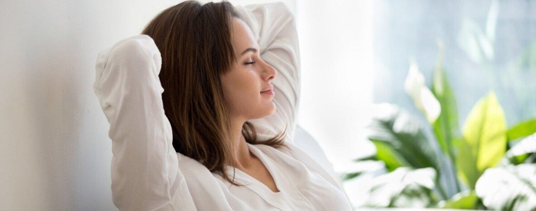 Eine Frau sitzt mit geschlossenen Augen und mit den Armen hinter dem Kopf verschränkt auf dem Sofa und atmet  tief durch