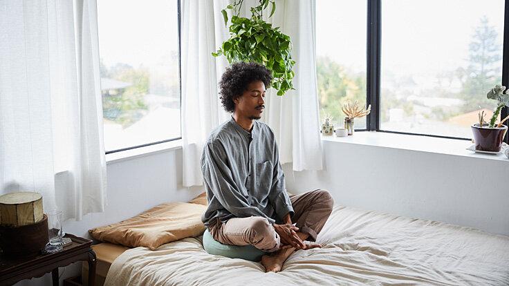 Ein Mann sitzt im Schneidersitz auf dem Bett und meditiert.