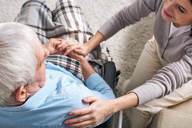 Hilfsbereite Angehörige sitzt neben einem älteren Mann im Rollstuhl und legt ihm die Hand auf die Schulter.