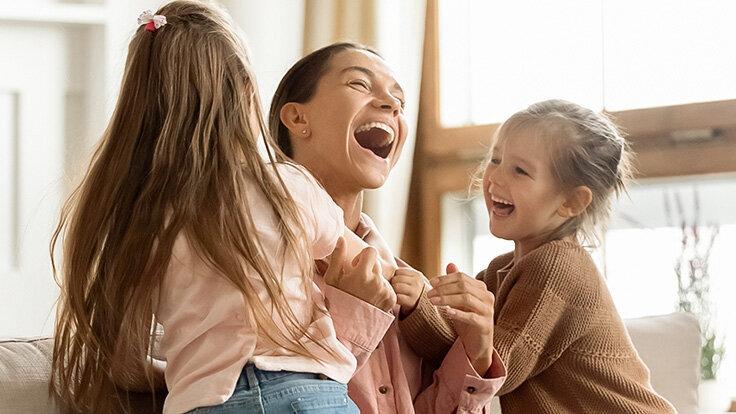 Mutter weiß, Lachen ist gesund und tobt fröhlich mit ihren zwei kleinen Kindern.