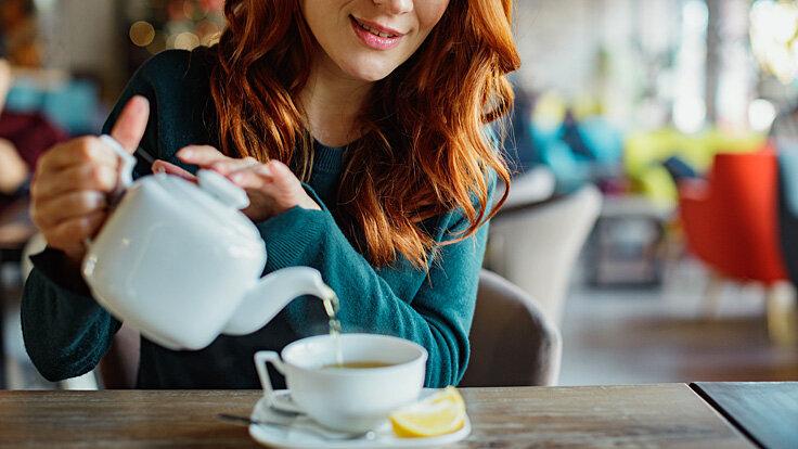 Eine Frau gießt sich Tee in eine Tasse ein.