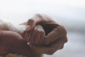 Mutter hält Neugeborenes im Arm