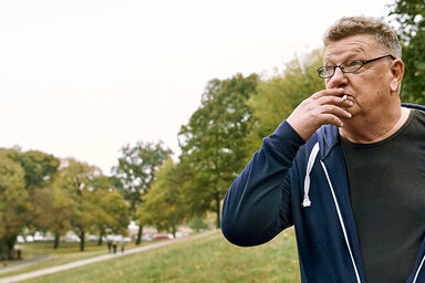 Mann in einer Sweatshirtjacke steht in einem Park und raucht.