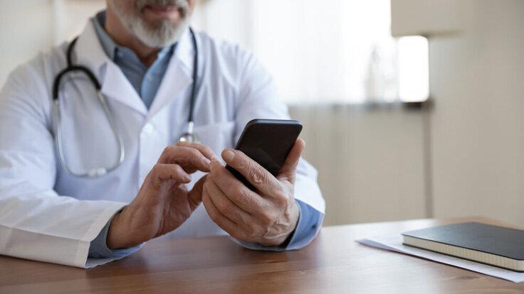 Arzt hält Smartphone in der Hand.