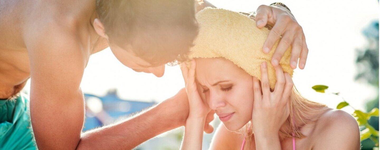 Mann legt einer Frau ein nasses Handtuch auf den Kopf.