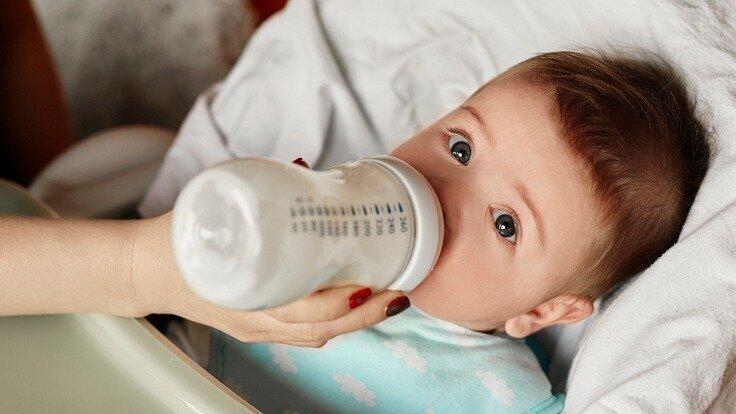Ein Baby trinkt aus einer sterilisierten Babyflasche.