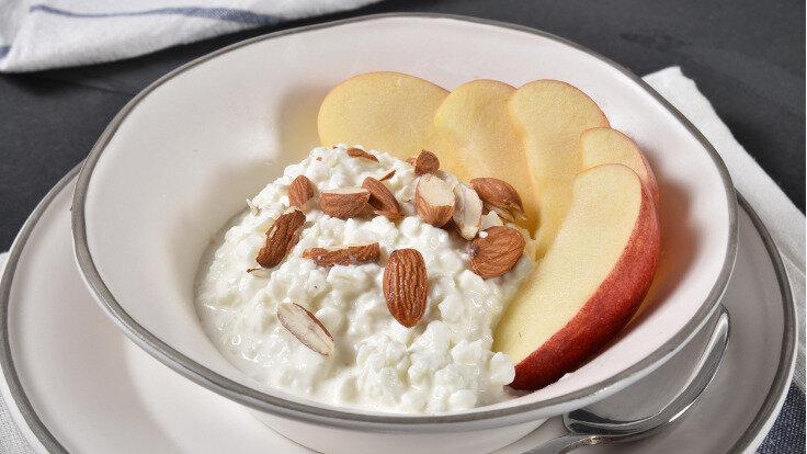 Hüttenkäse mit Obst und Mandeln in einer Schüssel als süßer und sättigender Low-Carb-Snack.