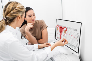 Eine Gynäkologin erklärt einer Frau, wie der weibliche Zyklus abläuft und funktioniert.