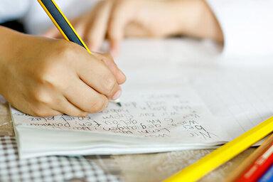 Ein Kind schreibt mit Handschrift seine Hausaufgaben.